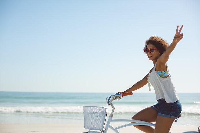girl riding bike along water